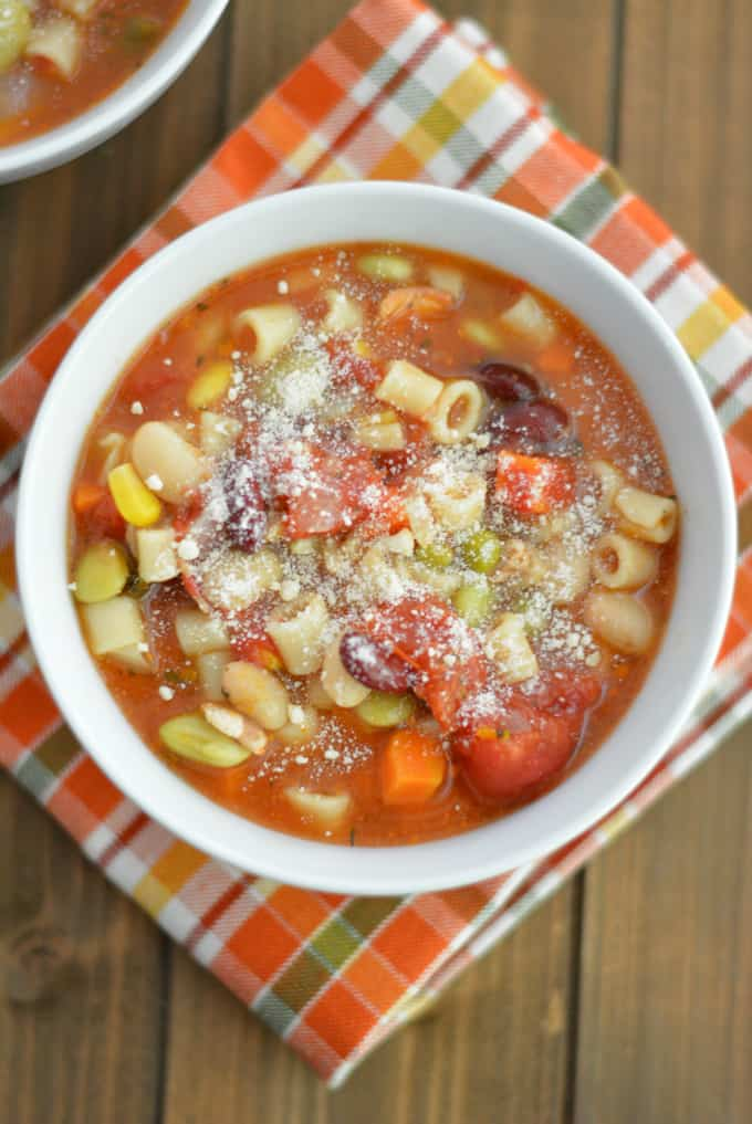 Minestrone Soup topped with Parmesan cheese on a wood table.
