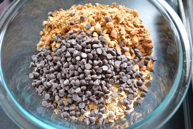 Chocolate chips, oats, and nuts in a glass bowl.