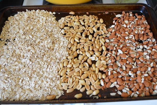 Energy bar ingredients, oats, peanuts, and almonds on a baking sheet.