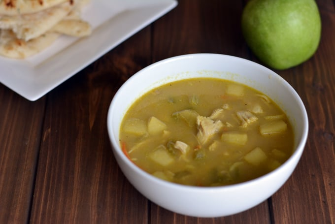 A white bowl filled with Indian mulligatawny soup next to a green apple and a white plate with Naan bread.