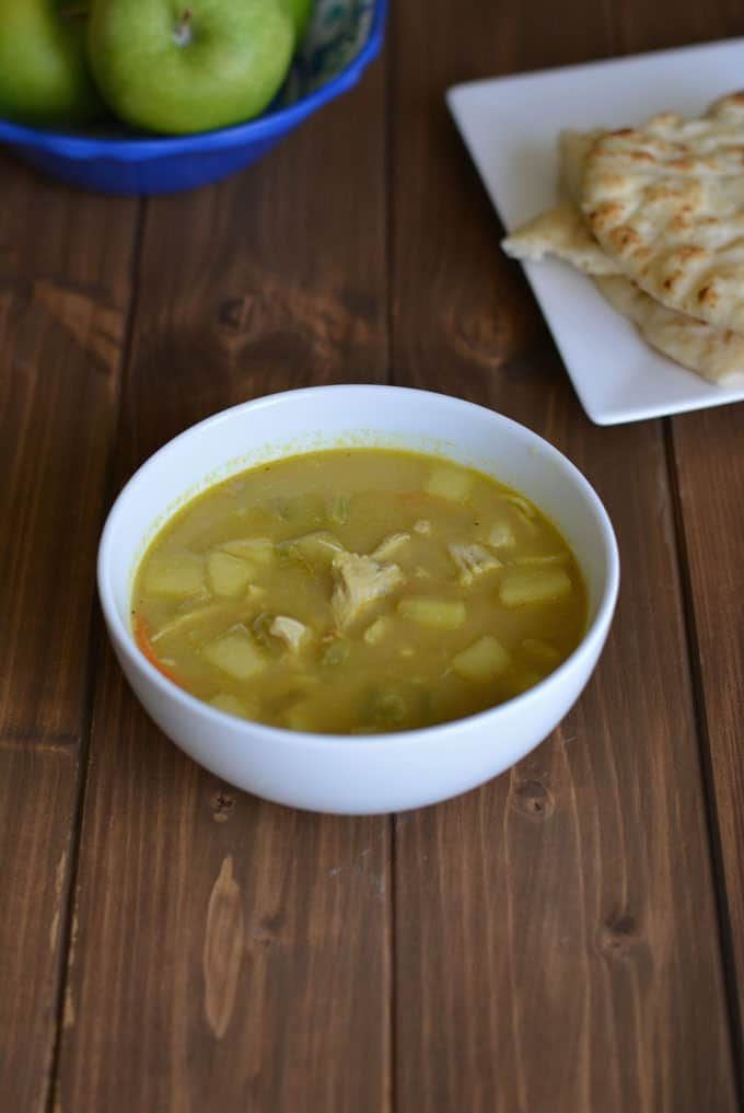 A bowl of Indian soup on a wood table with Naan bread and green apples