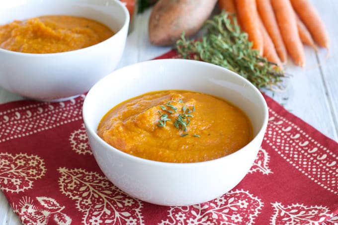 Roasted Carrot Sweet Potato Soup in a white bowl on top of a red napkin.