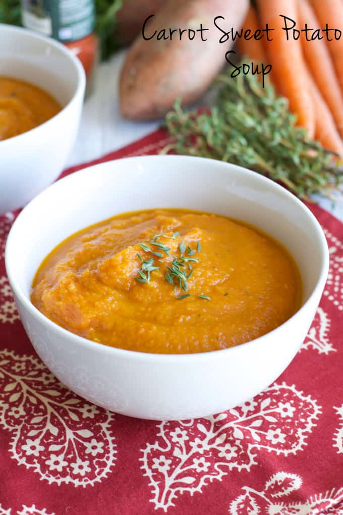Soup made with carrot and sweet potatoes roasted and pureed in a white bowl.