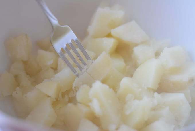 Mashing cooked potatoes with a fork.