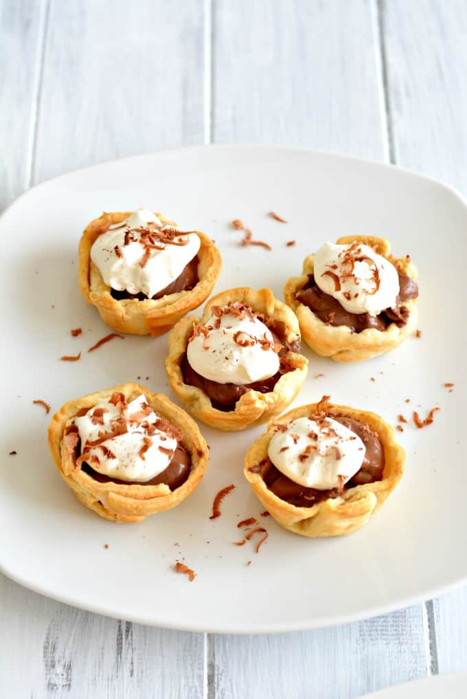 Five mini chocolate cream pies topped with whipped cream and chocolate shavings on a white plate.