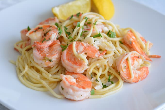 Lower calorie shrimp scampi over spaghetti with a lemon wedge on a white plate.