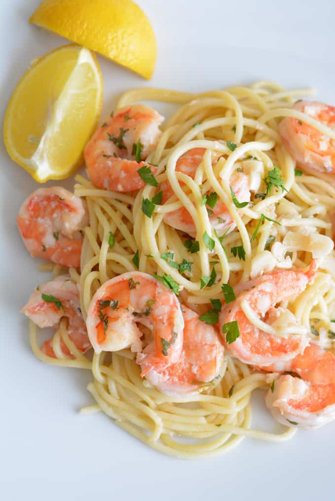 Shrimp scampi on a white plate with two lemon wedges.