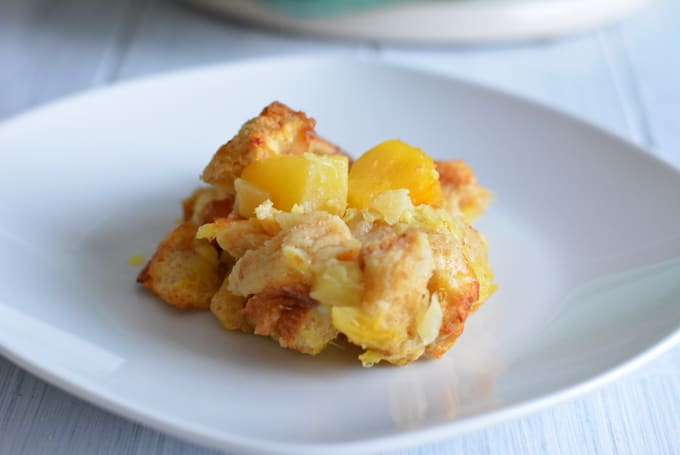 A spoonful of Lighter Pineapple Bread Casserole on a white plate.