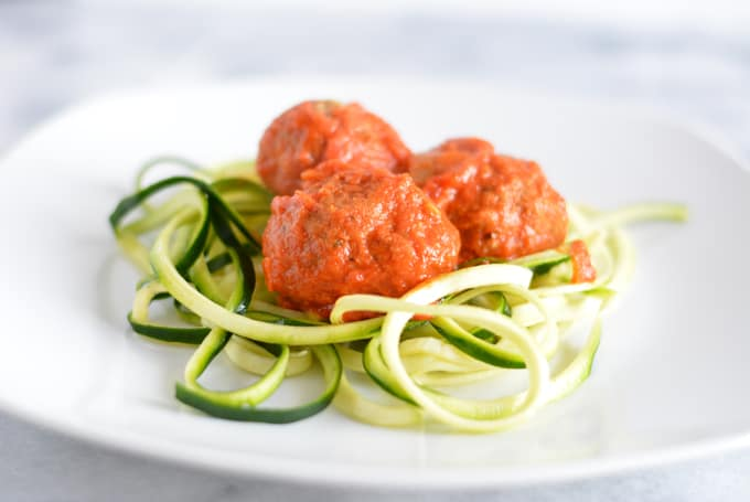 Meatless balls made with eggplant on top of zucchini noodles on a white plate.