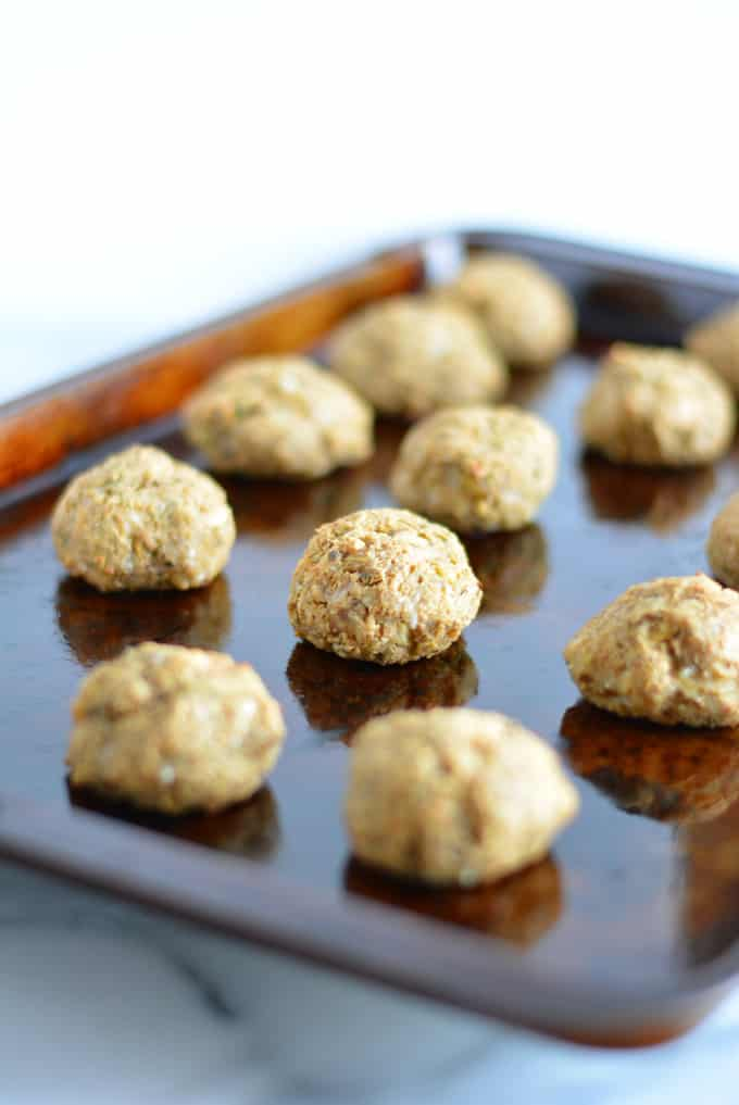 Vegetable balls made with eggplant on a baking sheet.