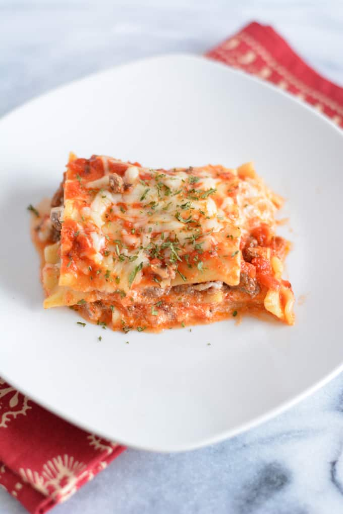 Lasagna with ground beef on a white plate.