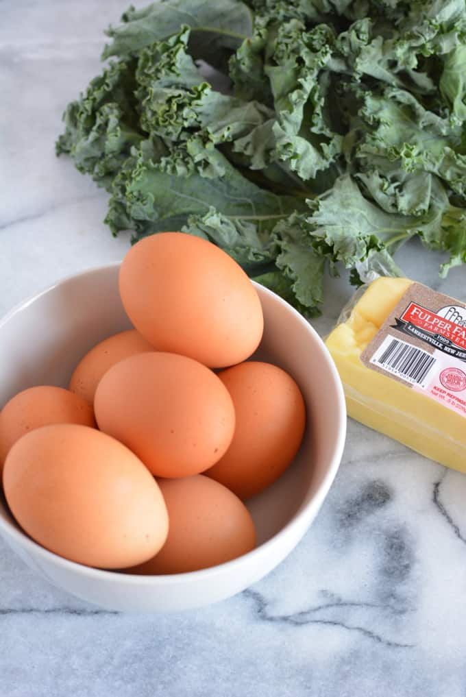 Brown eggs with a bunch of kale and block of cheese on a white marble table.