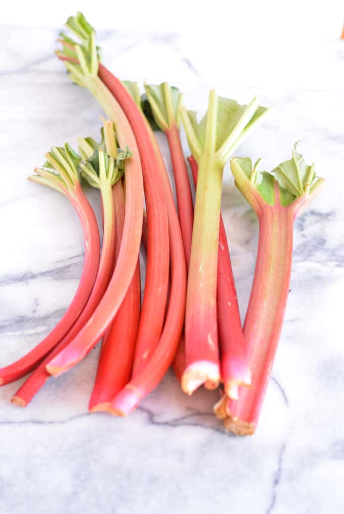 Stalks of Rhubarb laying on a white counter.