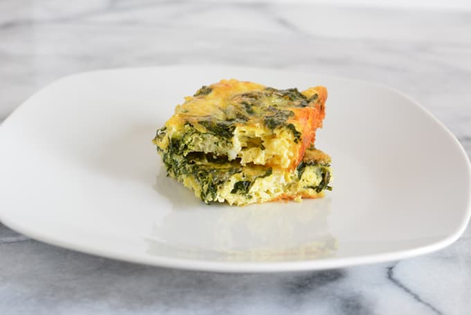 Two squares of a crustless fittata with kale on a white plate.