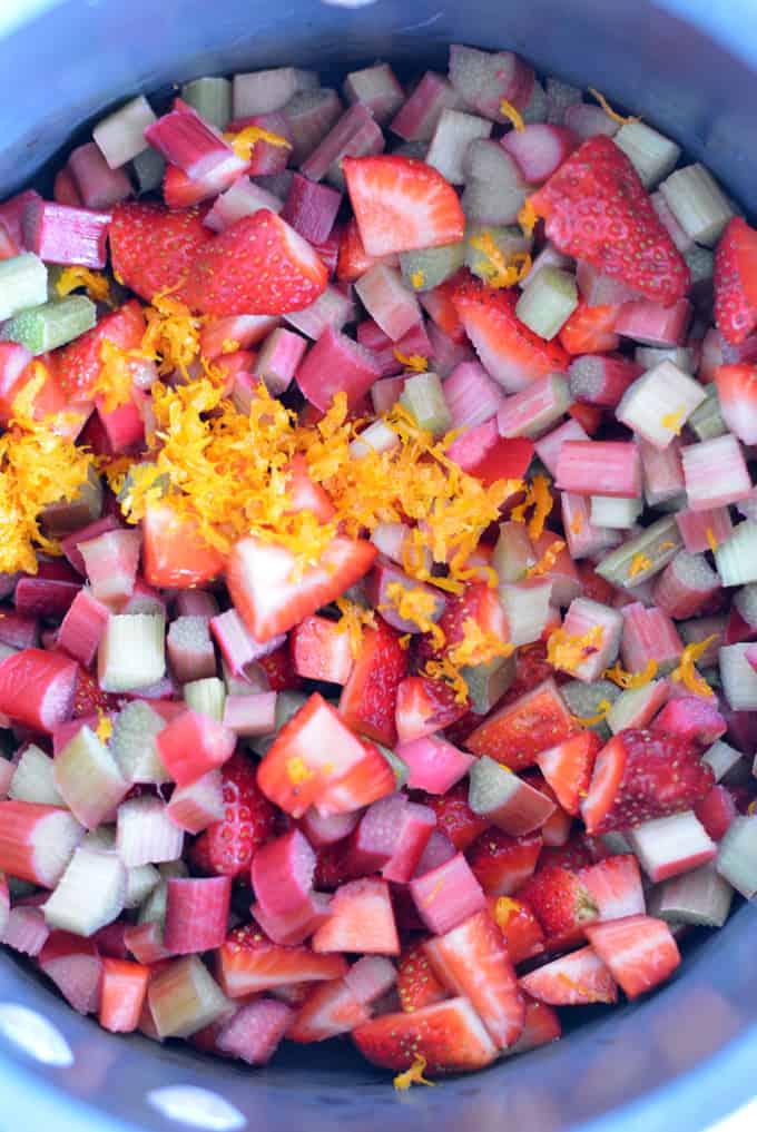 Rhubarb and strawberries diced in a pot with orange zest.