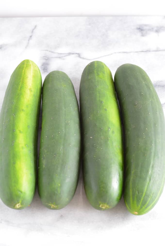 Four cucumbers on a white marble counter.