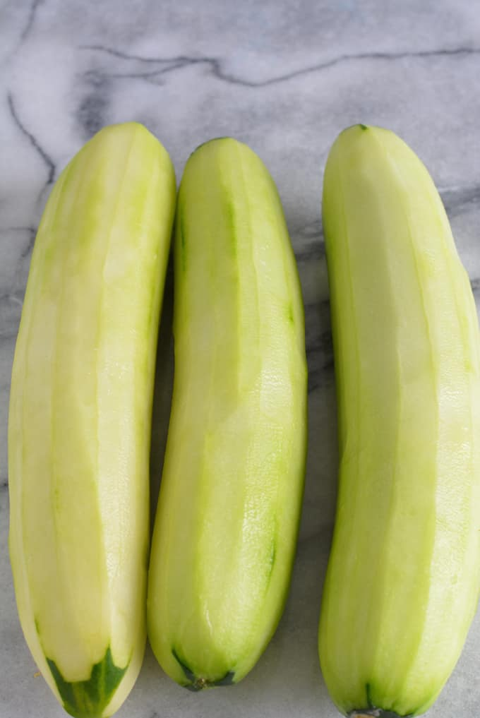 Three cucumbers peeled sitting on a white marble table.