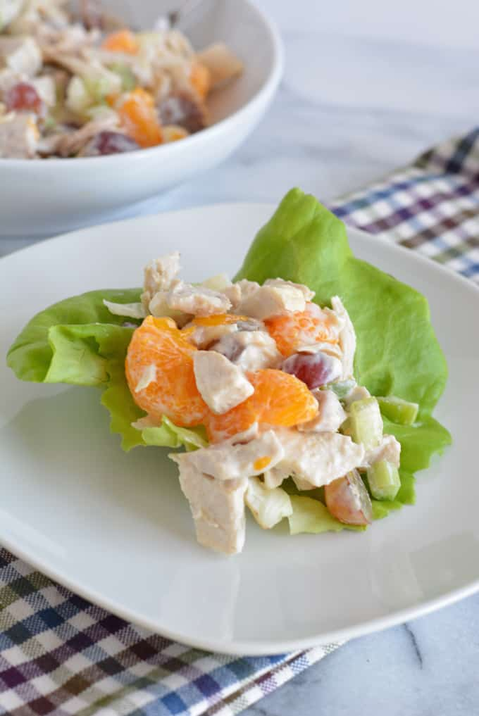 A scoop of chicken salad on top of butter lettuce on a white plate.