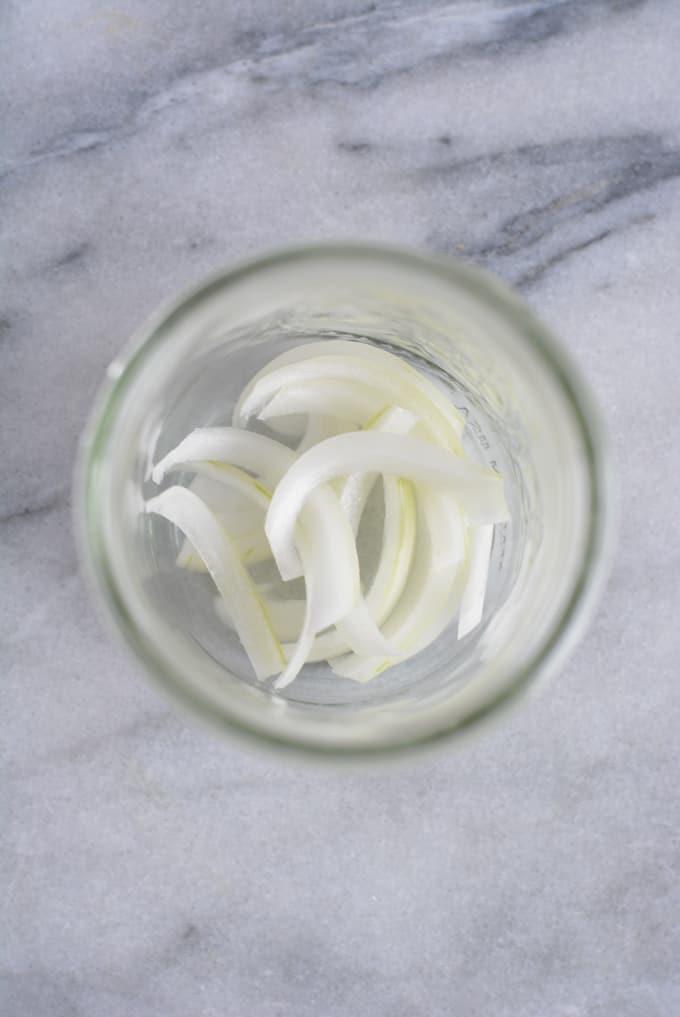 Onion slices inside a mason jar.