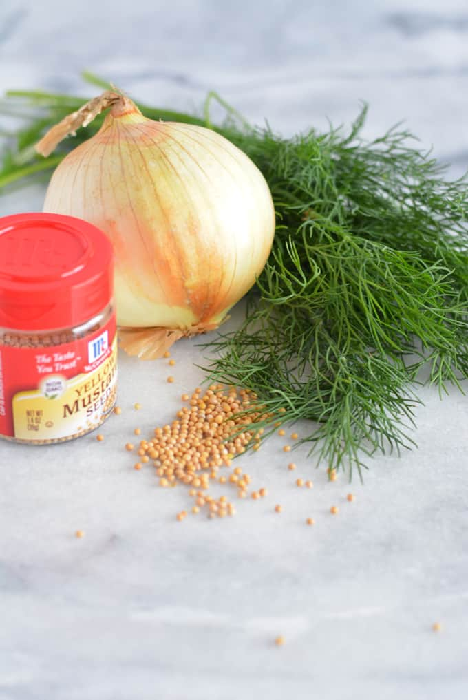 Fresh dill, onion, and mustard seed on a white counter.