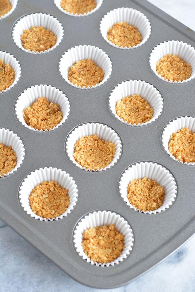 Graham cracker crust in a mini cupcake pan.