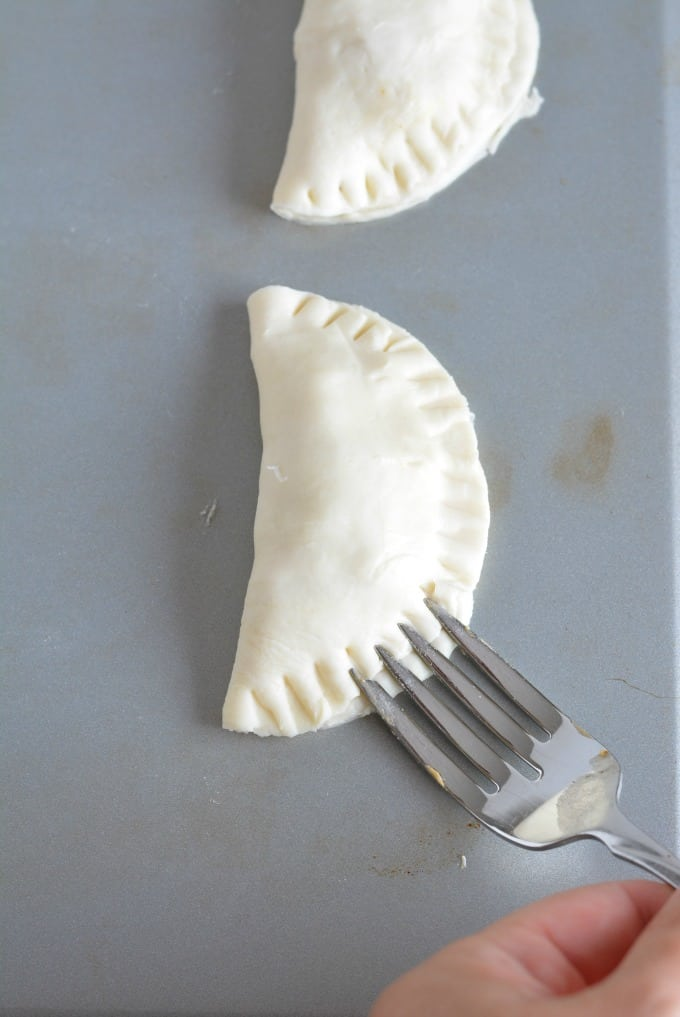 An uncooked Empanada being pressed closed with the back of a fork.
