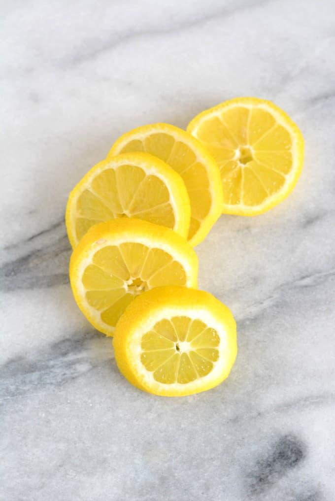 5 slices of fresh lemon on white marble table.