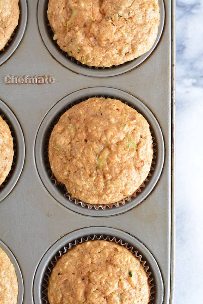 Zucchini muffins baked in a muffin pan.