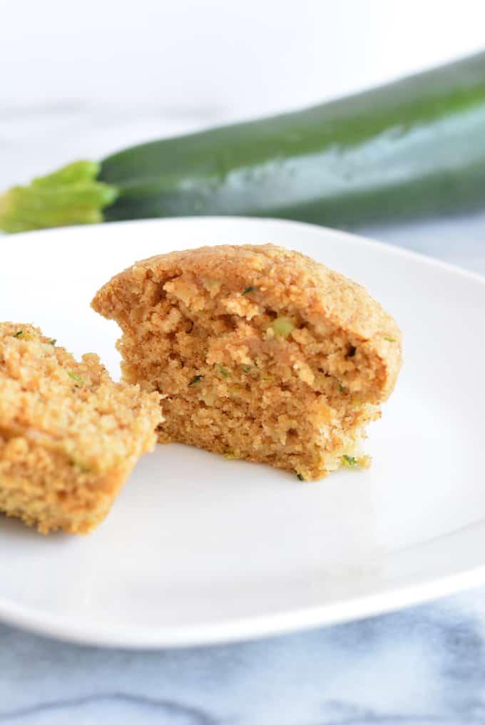 An oat bran zucchini muffin cut in half on a white plate.