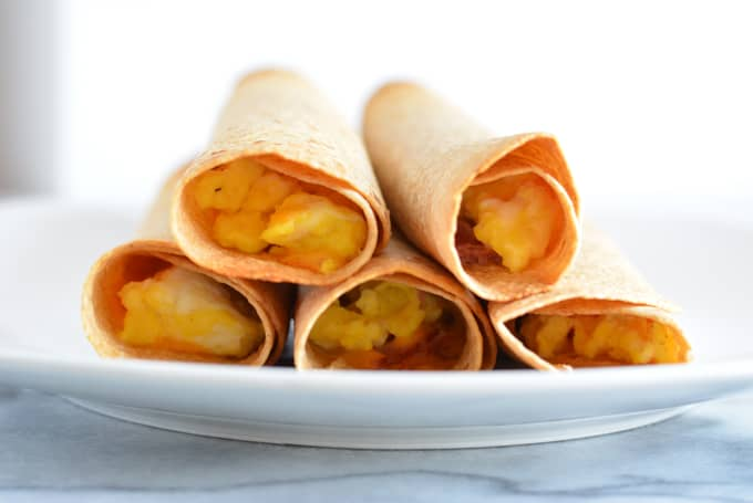 Ham & Cheese breakfast taquitos layers on a plate.