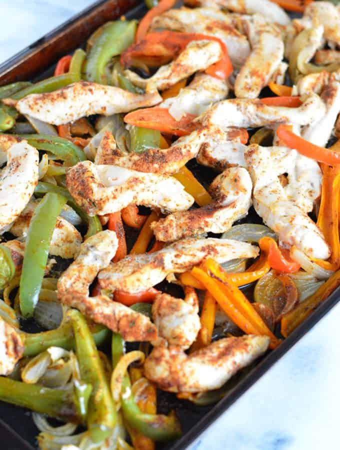 Chicken fajita mixture on top of a baking sheet.