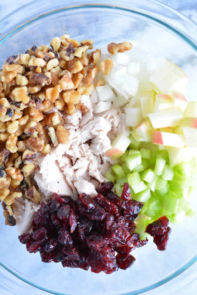 Diced turkey, walnuts, dried cranberries, celery, onion, and chopped apples in a glass bowl.