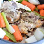 Chicken bones and vegetables in a pot.