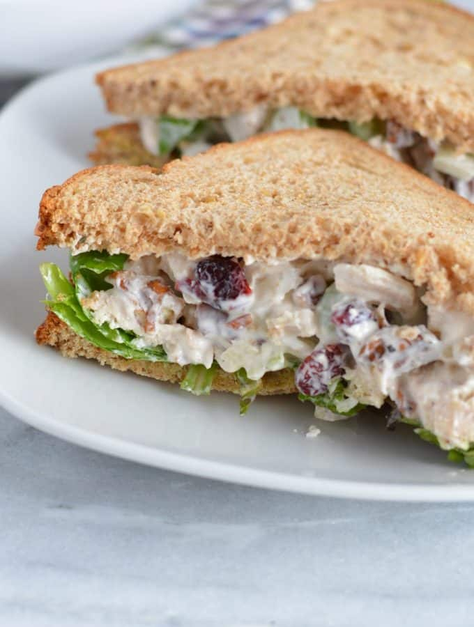 Chicken salad on whole wheat bread on a white plate.