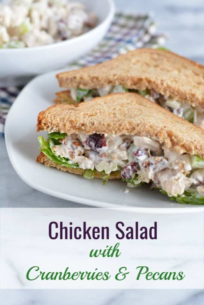 Pecan and cranberry chicken salad sandwich on wheat bread cut in half on a white plate.
