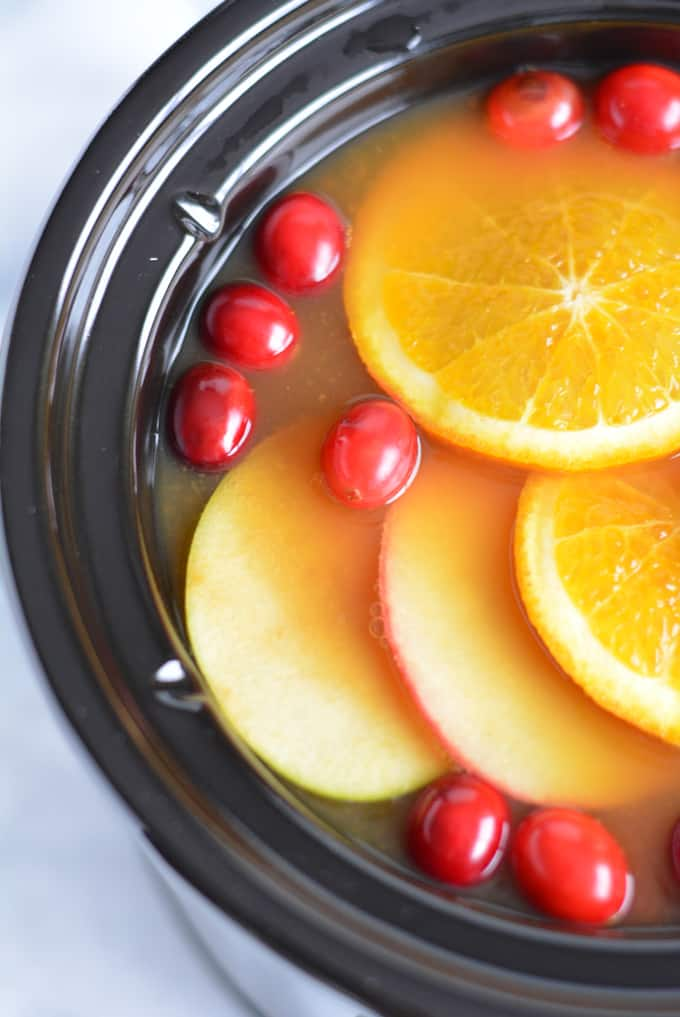 Hot apple cider with apple, oranges, and cranberries in a slow cooker