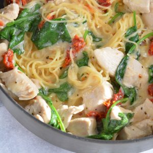 Pasta with chicken, spinach, and sun dried tomatoes in a pan.
