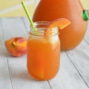 A glass of iced tea with a peach slice.